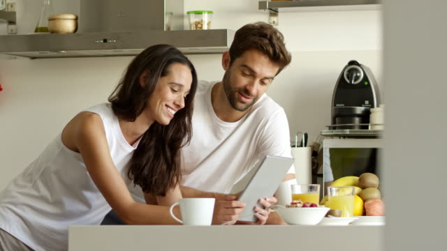 Do you remember that? 4k video footage of an affectionate young couple using a digital tablet in their kitchen young couple stock videos & royalty-free footage