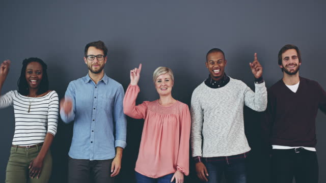 Do you see what we see? 4k footage of a group of happy designers pointing up while posing against a gray wall in studio pointing stock videos & royalty-free footage