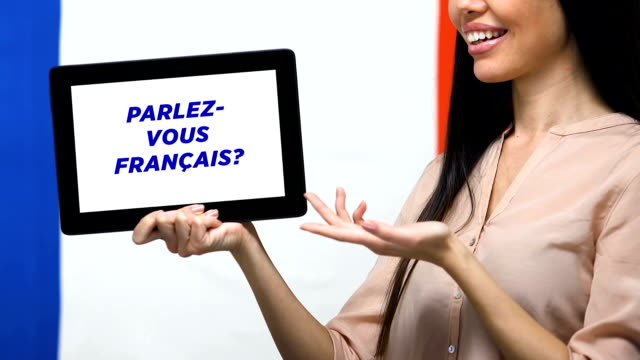 Do you speak French on tablet screen in female hand, language studying app