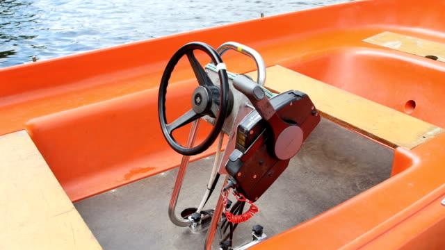 docked orange motoerboat in a lake - abbrustolito video stock e b–roll
