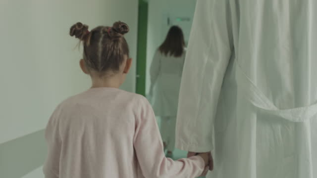 Doctor and girl holding hands and walking in hospital video