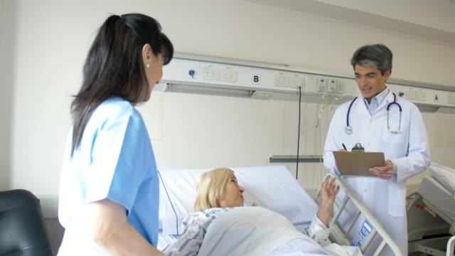 Doctor and nurse examining senior patient video