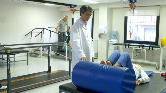 Doctor and nurse helping senior patients in rehab video
