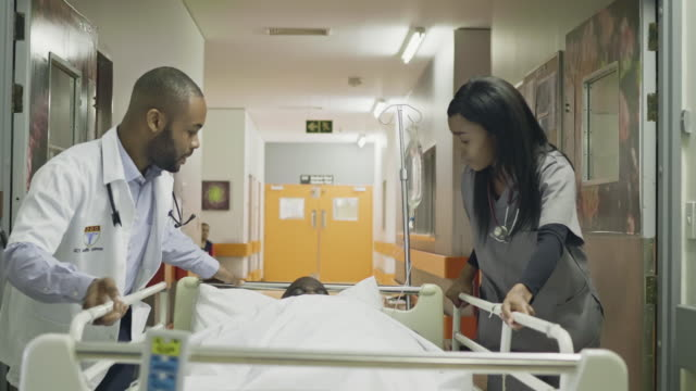 Doctor and nurse moving patient on stretcher Young doctor and nurse moving a patient on stretcher at hospital. stretcher stock videos & royalty-free footage