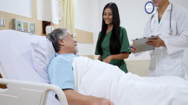 Doctor and nurse telling to senior patient the results of his medical tests. Doctor showing medical records to patient in hospital ward. Doctor explain the side effects of the intervention.
