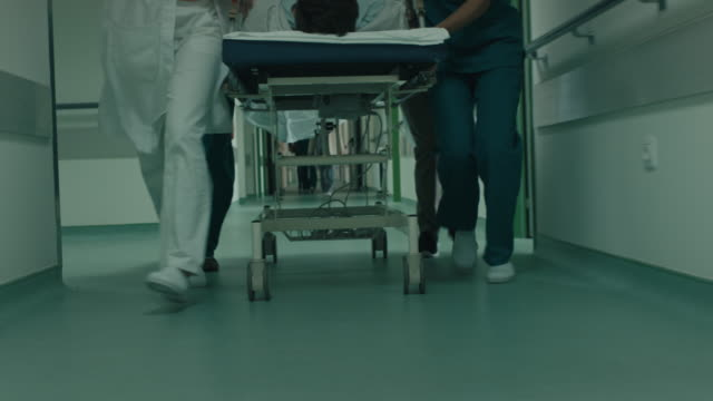 Doctor and nurses wheeling patient in gurney down hospital corridor