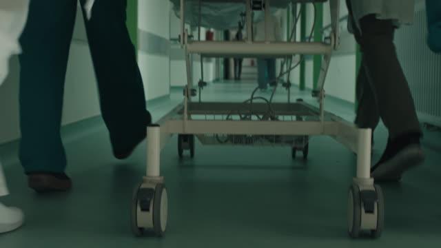 vídeos de stock e filmes b-roll de doctor and nurses wheeling patient in gurney down hospital corridor - important