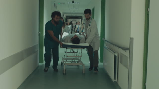 Doctor and nurses wheeling patient in gurney Doctor and nurses wheeling patient in gurney down hospital corridor stretcher stock videos & royalty-free footage