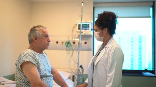 얼굴 마스크와 병원 방에서 의사와 환자 - 헌신 스톡 비디오 및 b-롤 화면