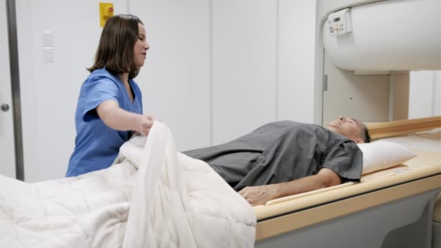 Doctor And Patient In MRI Lab At Medical Center Nurse talking with senior sick patient before MRI in medical laboratory inside hospital. Female staff worker speaking to ill old man in clinic before magnetic resonance imaging. Health care and people oncology stock videos & royalty-free footage