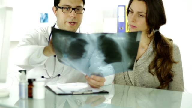 Doctor and Patient Looking at Xray Writing Prescription video
