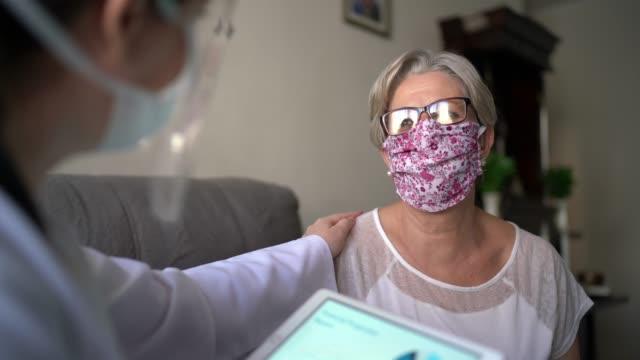 vidéos et rushes de docteur et patient sur la consultation médicale utilisant la tablette numérique à la maison du patient - medecin covid