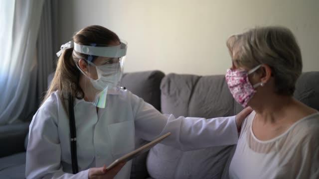 患者の家でデジタルタブレットを使用した医療相談の医師と患者 - 老人ホーム点の映像素材/bロール