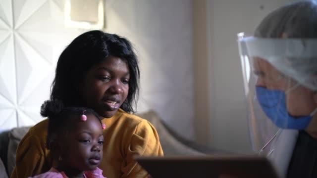 medico e pazienti (madre e figlia) in consultazione medica a casa del paziente - occhiali protettivi video stock e b–roll