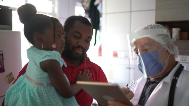doktor ve hastalar (baba ve kız) hastanın evinde tıbbi danışma - ziyaret stok videoları ve detay görüntü çekimi