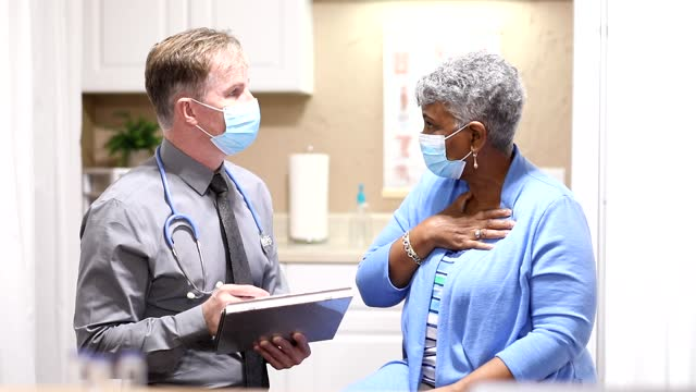 COVID-19: Doctor and senior adult, African descent patient, masks. video