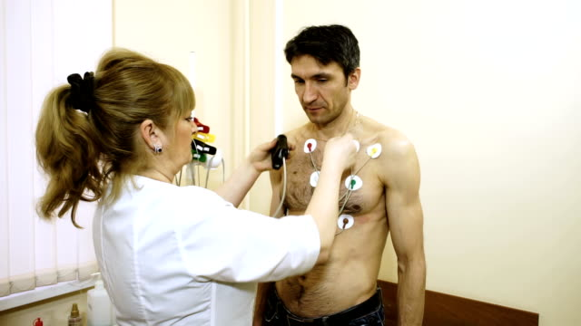 vídeos de stock e filmes b-roll de doctor attaching electrodes on patient's chest to monitor an electrocardiogram. - ventrículo do coração