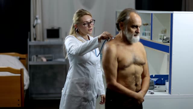 Doctor auscultating patient's back at clinic video
