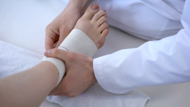 Doctor bandaging sprained ankle, running injury after workout, leg closeup Doctor bandaging sprained ankle, running injury after workout, leg closeup ankle stock videos & royalty-free footage