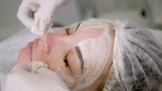 doctor beautician removes white cream from the face of his patient lying - kosmetyczka praca w salonie piękności filmów i materiałów b-roll