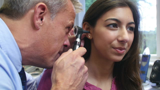 Doctor Carrying Out Ear Exam On Female Patient Doctor using otoscope to examine ear of young female patient.Shot on Sony FS700 at a frame rate of 25fps ear stock videos & royalty-free footage
