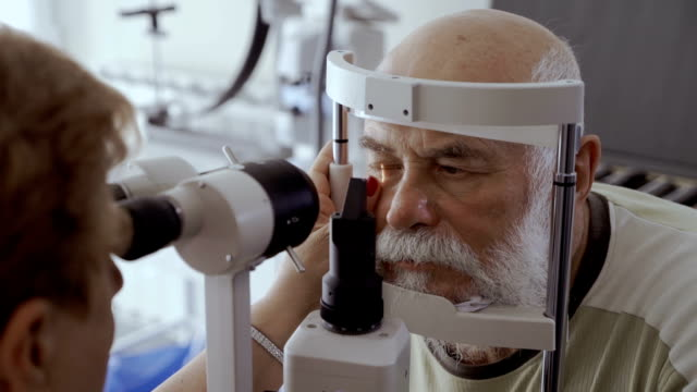 Doctor check eyesight of senior man with biomicroscope Doctor check eyesight of senior man with modern equipment. Old man look on the oculist and don't move his eyes. Diagnostic eyesight of pensioner. eyesight stock videos & royalty-free footage