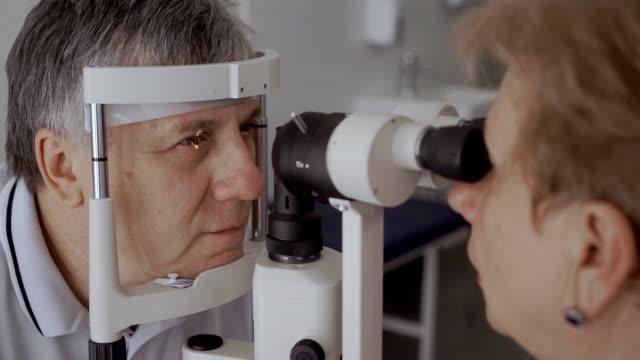 vidéos et rushes de médecin vérifier l'acuité visuelle d'un homme adulte avec un équipement moderne - rétine