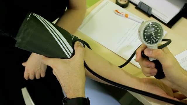 vídeos de stock e filmes b-roll de doctor checking blood pressure of a patient at hospital.close up - enfarte