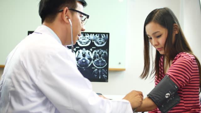 若い女性のチェック血圧を医師します。 - 健康診断点の映像素材/bロール