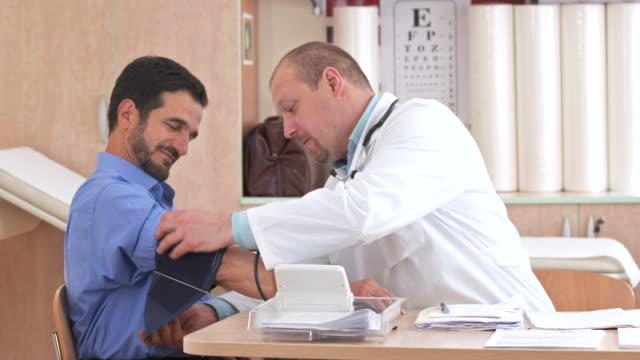 vídeos de stock, filmes e b-roll de hd: médico verificando pressão arterial - geriatria