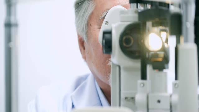 Doctor checking eyes of a senior male patient.Optician examining a patients eyes in ultra video