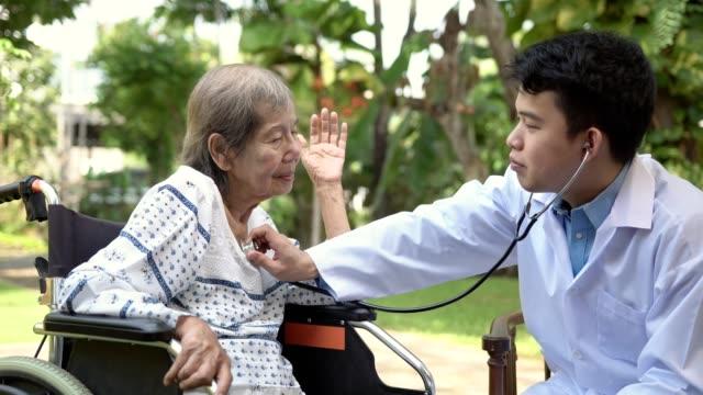ホームケア医療中の高齢女性の肺をチェックする医師 - 聴診器点の映像素材/bロール