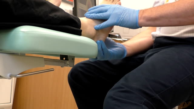 Doctor checking man's foot Doctor podiatrist is examining male patient's foot in his office ankle stock videos & royalty-free footage