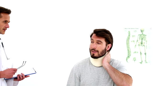 Doctor checking on injured patient in a neck brace video