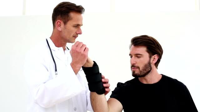 vídeos de stock, filmes e b-roll de médico verificando um paciente feridos no pulso de emergência - punho
