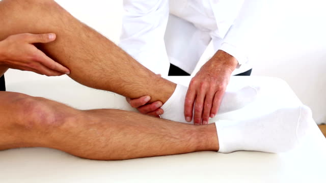 Doctor checking sportsmans injured ankle Doctor checking sportsmans injured ankle in his office at the hospital ankle stock videos & royalty-free footage