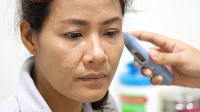 doctor checking temperature in women patient's ear with digital thermometer in hospital room. - ear talking video stock e b–roll