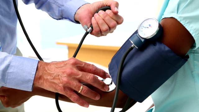Doctor checking the blood pressure of patient Doctor checking the blood pressure of patient in his office at the hospital blood pressure gauge stock videos & royalty-free footage