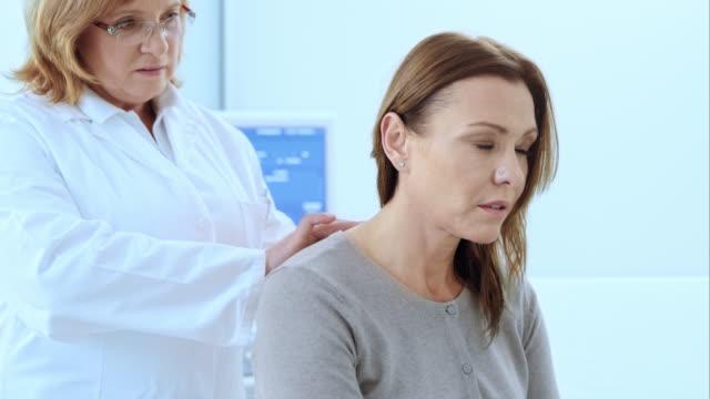 vídeos y material grabado en eventos de stock de doctor revisando los pacientes de sexo femenino de la columna - columna vertebral humana