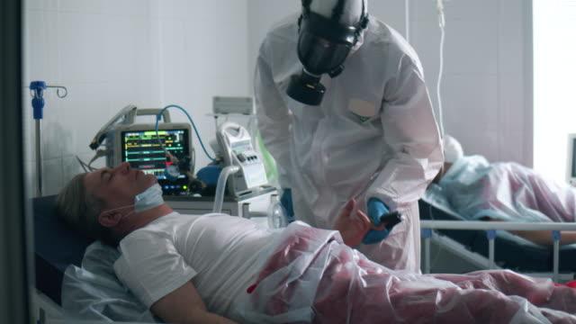stockvideo's en b-roll-footage met de arts controleert een patiënt met beademing in het ziekenhuis. - ventilator bed