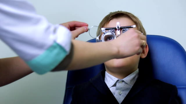 arzt prüft das sehvermögen mit diagnostischen linsen - medizinexamen stock-videos und b-roll-filmmaterial