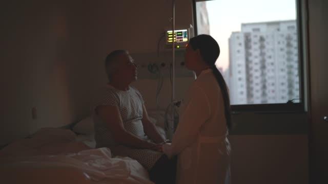 arzt consoling patient im krankenhauszimmer - geduld stock-videos und b-roll-filmmaterial