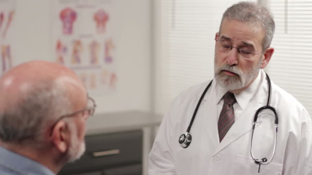 Doctor consulting with patient in exam room video