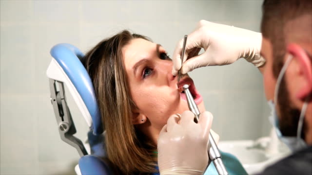 doctor dentist cleans teeth for young woman from plaque and tartar - orthodontist stock videos and b-roll footage