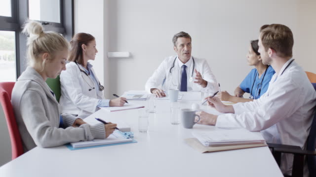 doctor discussing with colleagues in board room - collega d'ufficio video stock e b–roll