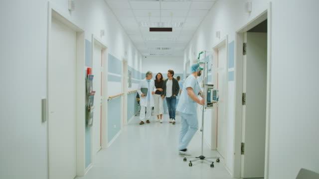 vidéos et rushes de docteur discutant avec le couple au couloir d'hôpital - couloir