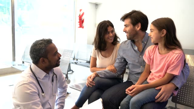 Doctor discussing with girl's family at hospital Doctor kneeling while discussing medical record with patient's parents. Healthcare worker is with girl's family in waiting room. They are talking at hospital. general practitioner stock videos & royalty-free footage
