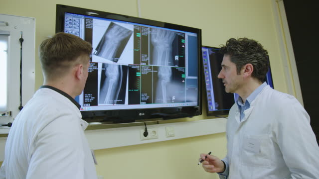 Doctor discussing x-ray results in office with a colleague Doctor discussing x-ray results in office with a colleague. Doctor standing by monitor screen and talking with a coworker in hospital. radiologist stock videos & royalty-free footage