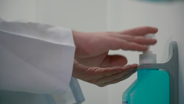 Doctor disinfect hands with gel