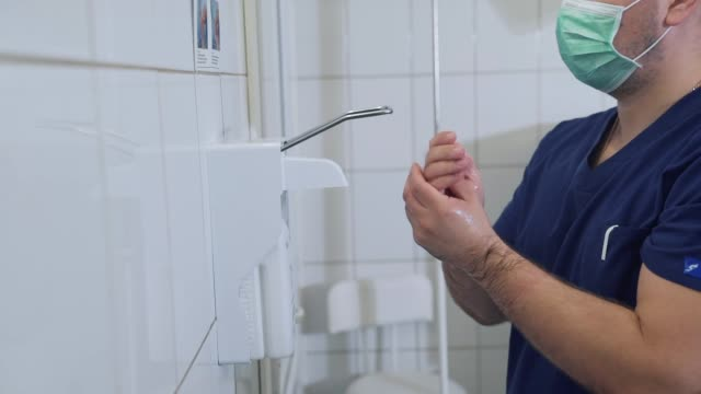 doctor disinfects and washing his hands dry before entering the operating room. surgical hand disinfection. emergency care. surgery detail in hospital or clinic - autoclave video stock e b–roll